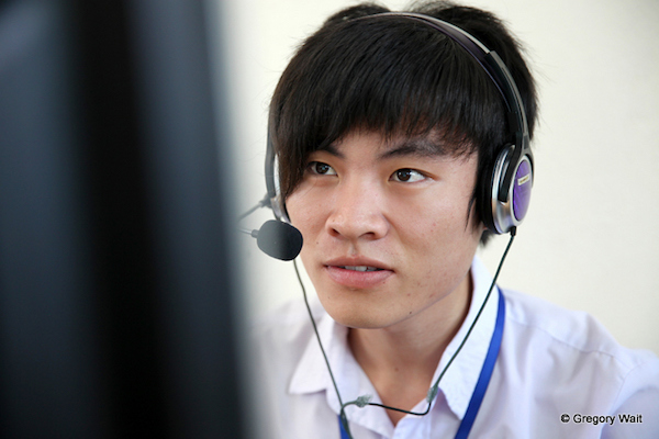 PNV student working on a computer with a headset on.