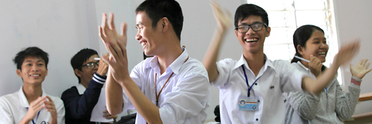 PNV group of students in a classroom clapping and smiling.