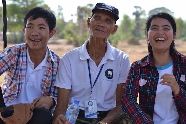 Photo of Mister YUM and two students on a swing laughing during the visit of the CEDAC Organic Farm in Takeo Province Cambodia.